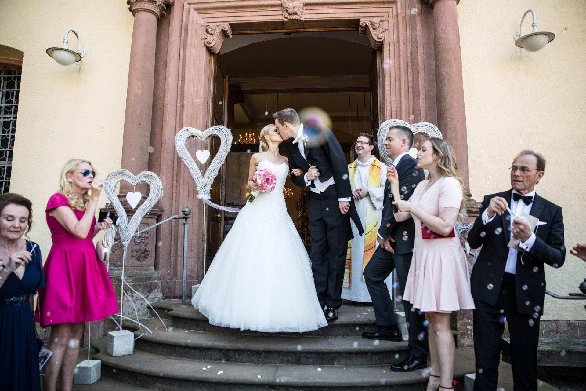 """<img src=""""hochzeitsfoto_vor_kirche.jpg"""" alt=""""hochzeitsfoto vor kirche küsst sich das brautpaar>"""